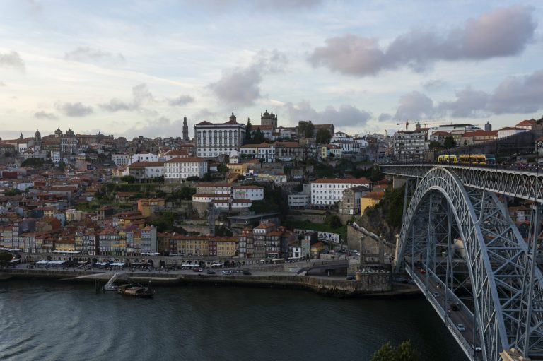 Beutiful Porto view, with Dom Luís Bridge and metro. Sunset, blue sky and clouds. Boats on the river.