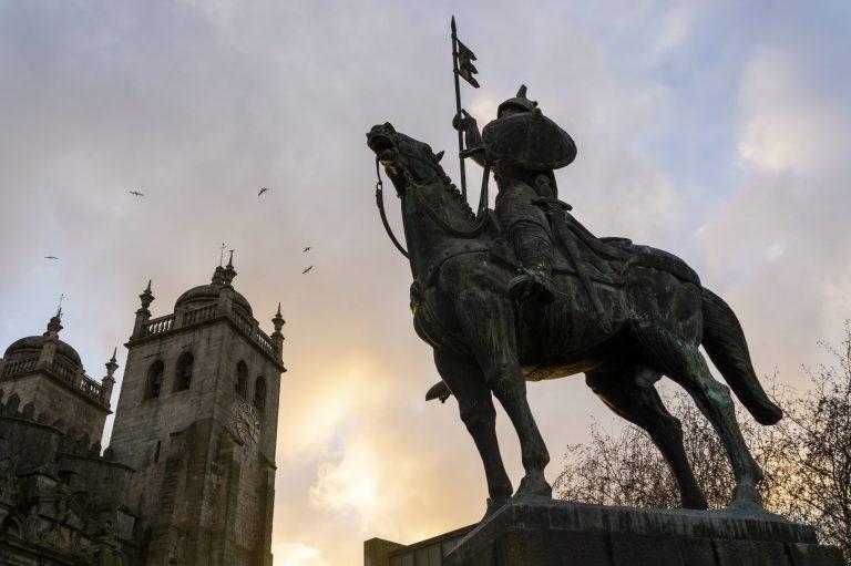 Warrior statue and cathedral of Porto in the background. Vímara Peres warrior. Porto, Portugal.