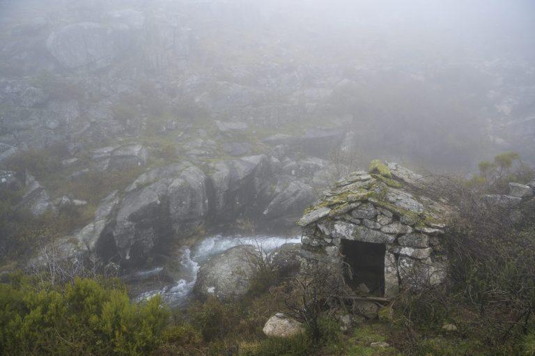 Old stone water mill. Mountain fresh water stream. Foggy day. Freita mountain range. Portugal