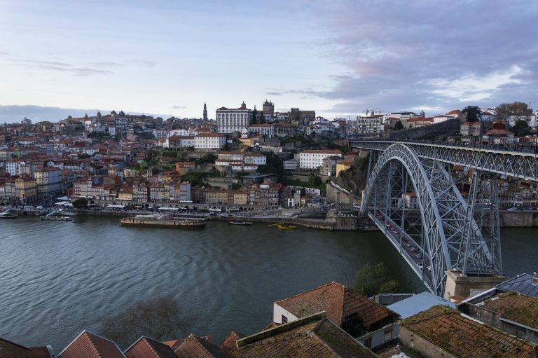 Porto, Portugal - 02/25/2020: Porto view, with Dom Luís Bridge and Douro river. Sunset, blue sky and clouds. Boats on the river